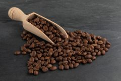 Roasted Coffee Beans Spilling from a Wooden Scoop stock photos