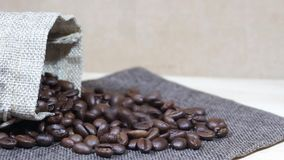 Roasted coffee beans tumbling down into pile of coffee beans next to burlap sack. Video footage of roasted coffee beans tumbling down into pile of coffee beans stock video footage