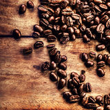 Roasted  coffee beans on vintage table. Coffee on grunge wooden Royalty Free Stock Photos