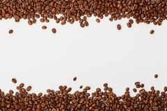 Roasted coffee beans on white background. Frame template with copy space, top view stock images