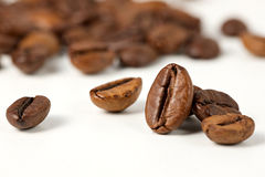 Roasted coffee beans on a white background, selective focus. Group of roasted coffee beans on a white background, selective focus. Blurred background Royalty Free Stock Image