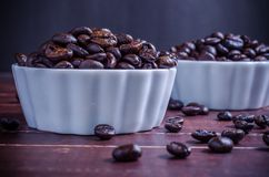 Roasted coffee beans in white bowl porcelain on wooden backg Stock Photo