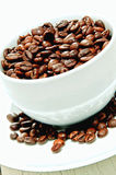 Roasted coffee beans in a white cup Royalty Free Stock Photos