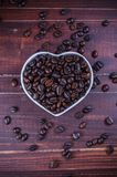 Roasted coffee beans in white heart bowl porcelain Royalty Free Stock Images