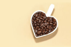 Roasted Coffee beans in a white heart shape cup Stock Photography