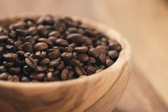 Roasted coffee beans in wood bowl on table Stock Photo