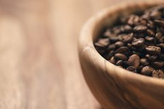 Roasted coffee beans in wood bowl on table Stock Image