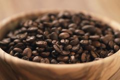 Roasted coffee beans in wood bowl on table Royalty Free Stock Photo