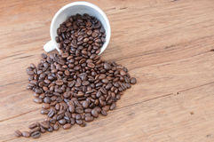 Roasted coffee beans on wood table Royalty Free Stock Images