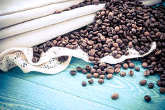 Roasted coffee beans in wooden basket and linen napkin with laceson a wooden background stock image