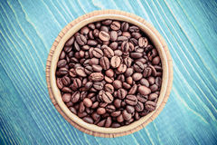 Roasted coffee beans in wooden basket on a wooden background stock photos