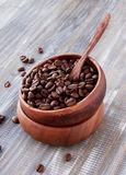Roasted coffee beans in wooden bowl, selective focus Stock Image