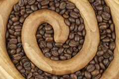 Roasted coffee beans in a wooden spiral on the canvas background. Fresh roasted coffee. Stock Photography