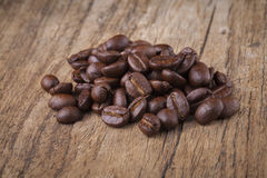 Roasted coffee beans in wooden spoon placed on coffee beans as b. Roasted coffee beans in wooden spoon placed Royalty Free Stock Image