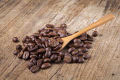 Roasted coffee beans in wooden spoon placed on coffee beans as b. Roasted coffee beans in wooden spoon placed Stock Photos