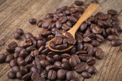 Roasted coffee beans in wooden spoon placed on coffee beans as b. Roasted coffee beans in wooden spoon placed Stock Photo