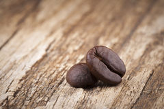 Roasted coffee beans in wooden spoon placed on coffee beans as b. Roasted coffee beans in wooden spoon placed Royalty Free Stock Photography