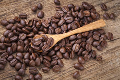 Roasted coffee beans in wooden spoon placed on coffee beans as b. Roasted coffee beans in wooden spoon placed Stock Images