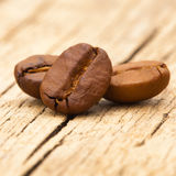 Roasted coffee beans on wooden table - close up shot Royalty Free Stock Photos