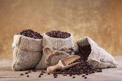 Roasted coffee in burlap bags. Roasted coffee beans in burlap bags on old wooden table stock images