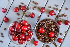 Roasted coffee grains next to red cherries on a light background. Fruit flavor favorite drink. Roasted coffee grains next to red cherries on a light background royalty free stock photo
