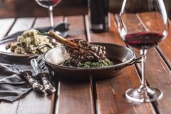 Roasted or confit Lamb Leg in pan with spinach and red wine.  royalty free stock image