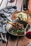 Roasted or confit Lamb Leg in pan with spinach and red wine.  royalty free stock photography