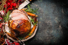 Roasted cortó el jamón de la Navidad en la placa con la bifurcación, el cuchillo y la decoración festiva en fondo rústico oscuro Imagen de archivo libre de regalías