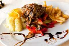 Roasted cutlet of veal with mushrooms and french f Stock Images