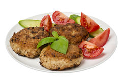 Roasted cutlets with tomatoes and cucumbers on the plate isolated. Royalty Free Stock Photo