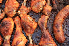 Roasted drumsticks and sausage. Royalty Free Stock Photo