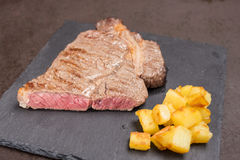 Roasted dry aged rib eye beef steak. With fried potatoes Royalty Free Stock Images