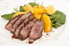 Roasted Duck Breast With Orange. And rocket served on a white plate Stock Image