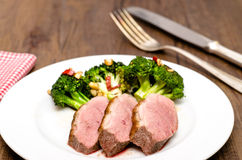 Roasted duck breast with rind. Green broccoli and chili peppers royalty free stock photography