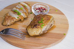 Roasted duck breast. Sliced roasted duck breast on wooden board Royalty Free Stock Image