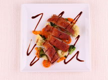 Roasted duck breast, vegetables, black sauce Stock Images