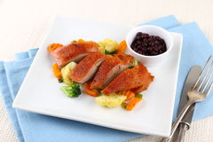 Roasted duck breast with vegetables and cutlery Stock Images