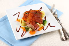 Roasted duck breast, vegetables and cutlery Stock Photo