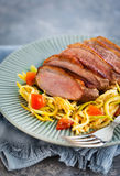 Roasted duck breast and zucchini noodles with tomatoes Stock Photos