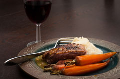 Roasted duck dinner. Roasted duck breast in orange sauce with carrots and celeriac mash. Served on a dark wooden table with a glass of red wine Royalty Free Stock Images