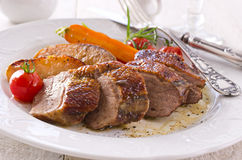 Roasted Duck Fillet with Apples. As closeup on a white plate royalty free stock photo