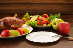 Roasted duck with fresh vegetables and apples and empty plate on Stock Images