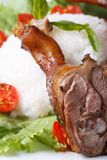 Roasted duck leg on a background of rice and vegetables Royalty Free Stock Image