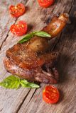 Roasted duck leg with basil and cherry tomatoes close up vertica Stock Images