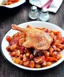 Roasted duck leg with Cassoulet beans, onions, bacon, carrots with fried pork sausage Stock Image