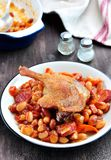 Roasted duck leg with Cassoulet beans, onions, bacon, carrots with fried pork sausage Royalty Free Stock Image