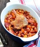 Roasted duck leg with Cassoulet beans, onions, bacon, carrots with fried pork sausage Stock Photography