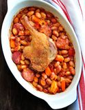 Roasted duck leg with Cassoulet beans, onions, bacon, carrots with fried pork sausage stock photo