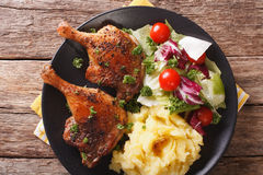 Roasted duck leg with mashed potatoes side dishes and fresh sala Royalty Free Stock Images