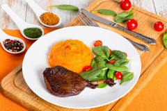 Roasted duck leg with mashed pumpkin and salad Royalty Free Stock Photography